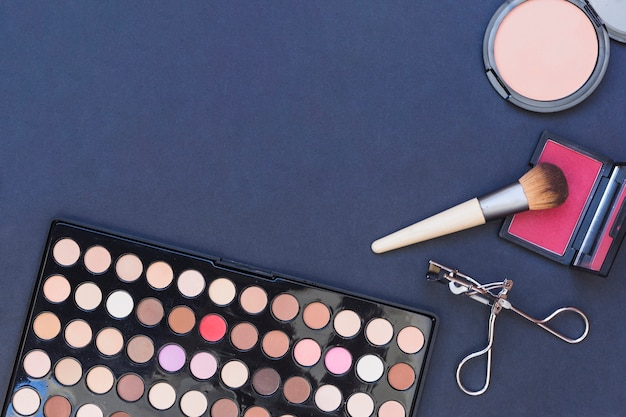 An overhead view of makeup brush; blusher; eyeshadow palette and eyelash curler on blue backdrop