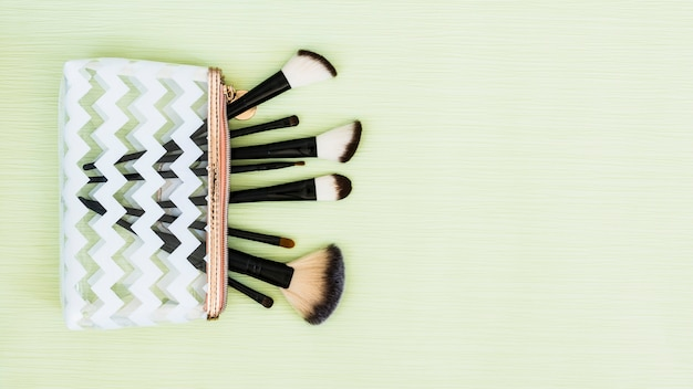 An overhead view of makeup brushes on mint green backdrop