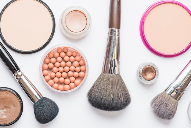 Overhead view of makeup kit and brushes on white backdrop
