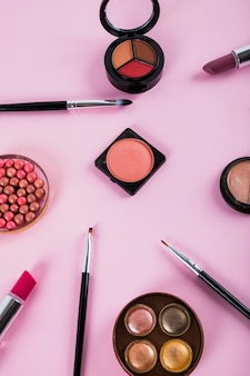 Overhead view of makeup kit with brushes on pink backdrop