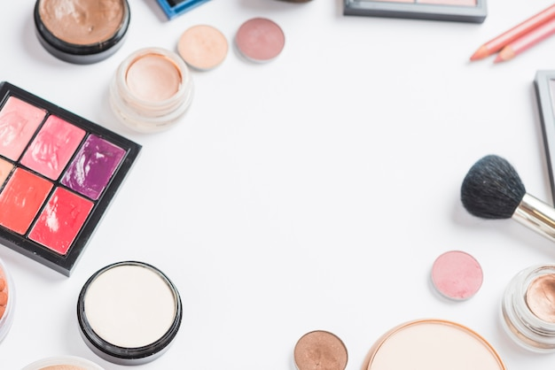 Overhead view of makeup products on white backdrop