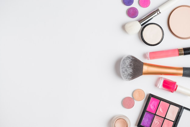 Overhead view of makeup products on white background