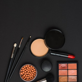 Overhead view of makeup products with brushes on black backdrop