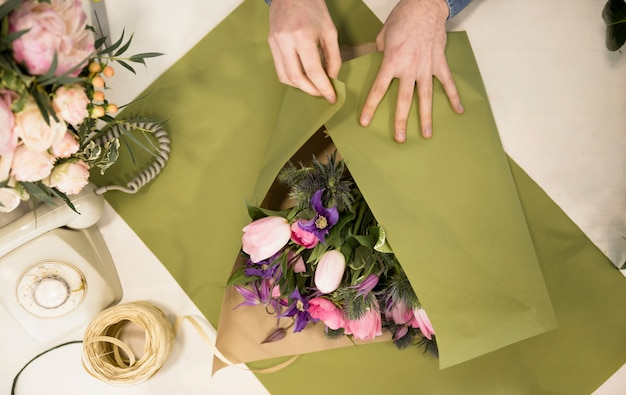 An overhead view of a male florist wrapping the flower bouquet with green paper on table