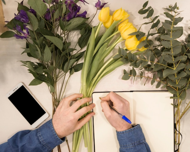 An overhead view of a male florist writing on diary with pen on table with flowers