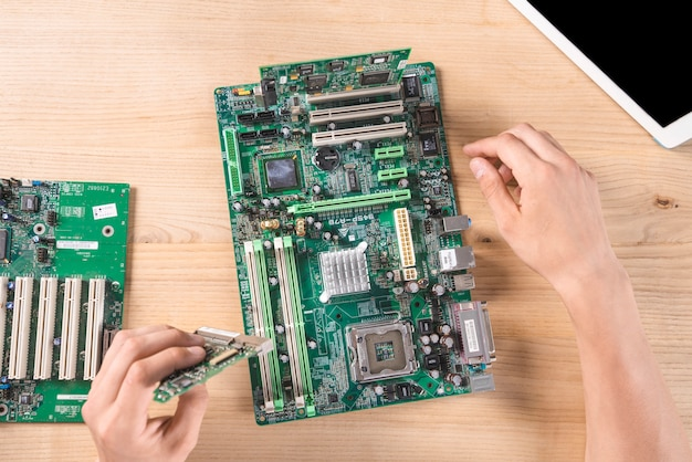 Overhead view of male it technician repairing circuit board on wooden table