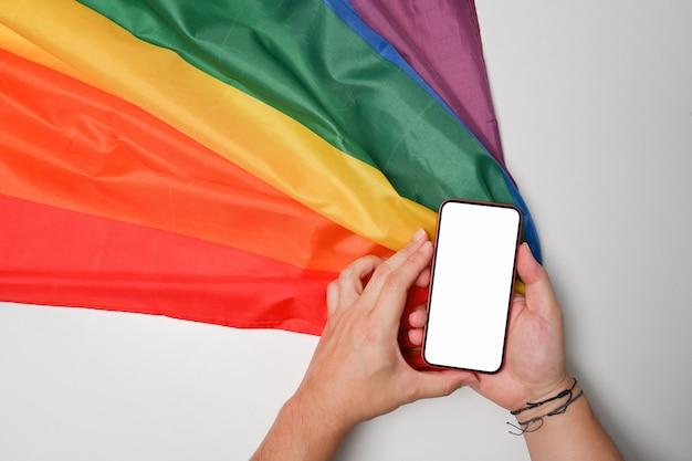 Вид сверху человек, держащий смартфон и радужный флаг на белом фоне.
