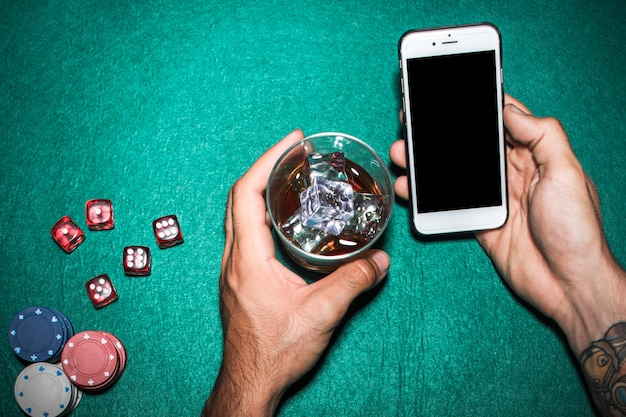 Overhead view of man's hand holding cellphone and whisky glass over the poker table