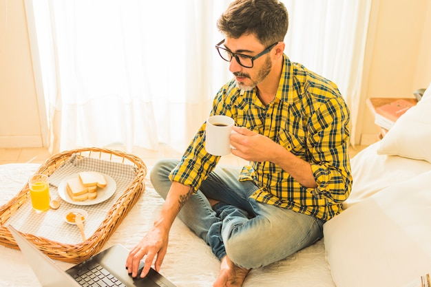 An overhead view of a man sitting on bed holding cup of coffee using laptop