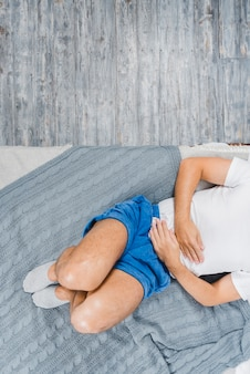 An overhead view of a man wearing sock lying on bed suffering from stomach pain