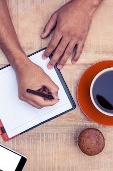 Overhead view of man writing on diary at table by coffee and cup cake