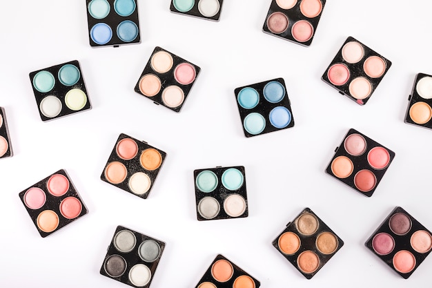 Overhead view of many eye shadow powders on white backdrop