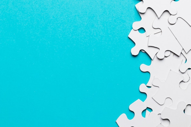 Overhead view of many white jigsaw puzzle pieces on blue surface