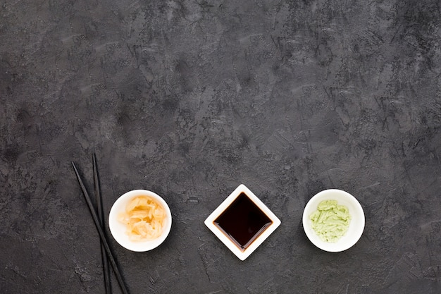 An overhead view of marinated ginger; wasabi and soya sauce with chopstick over blackboard