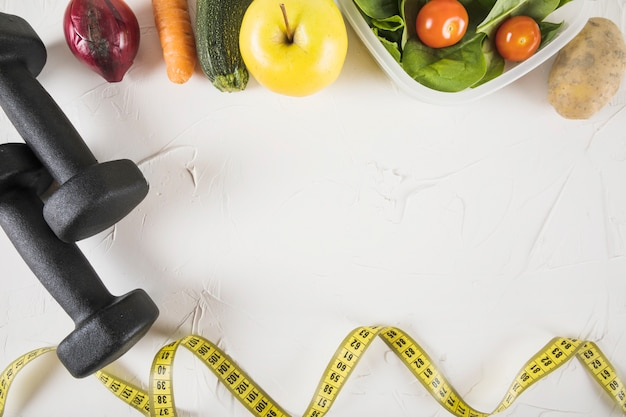 Overhead view of measuring tape; food and dumbbell on white backdrop