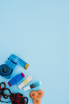 An overhead view of measuring tape; wool; spools and buttons on the corner of blue background