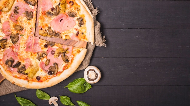 An overhead view of meat pizza with mushroom and basil leaf on wooden plank
