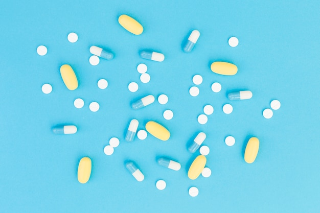 An overhead view of a medical pills on blue background