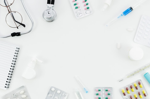 An overhead view of medical pills and equipment's on white background