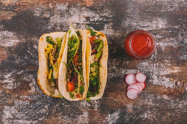 Overhead view of mexican beef tacos with vegetables and tomato sauce over old wooden background