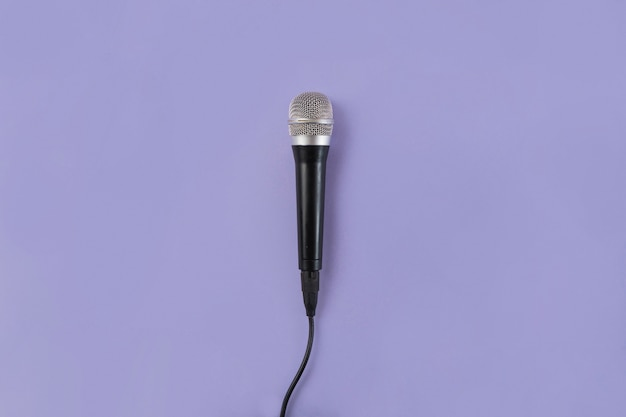 An overhead view of microphone on purple background
