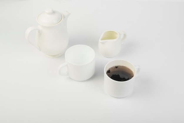 An overhead view of milk; tea and teapot on white background