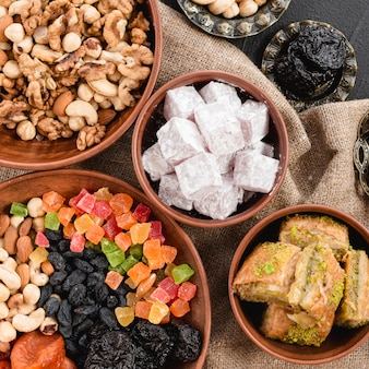 An overhead view of mixed nuts; dried fruits; lukum and baklava in earthen bowl for ramadan