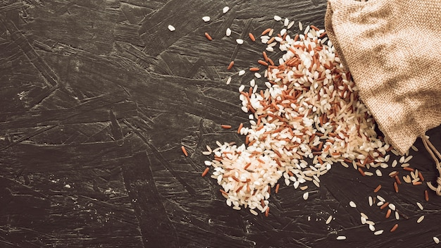 Overhead view of mixed rice grains spilling from sack