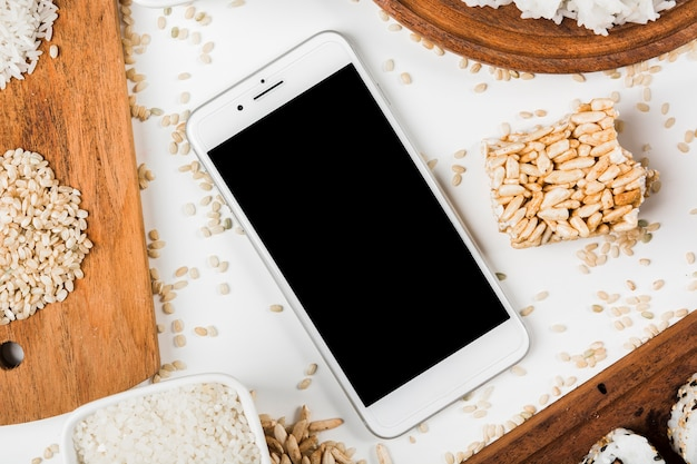 An overhead view of mobile phone surrounded with variety of uncooked and puffed rice