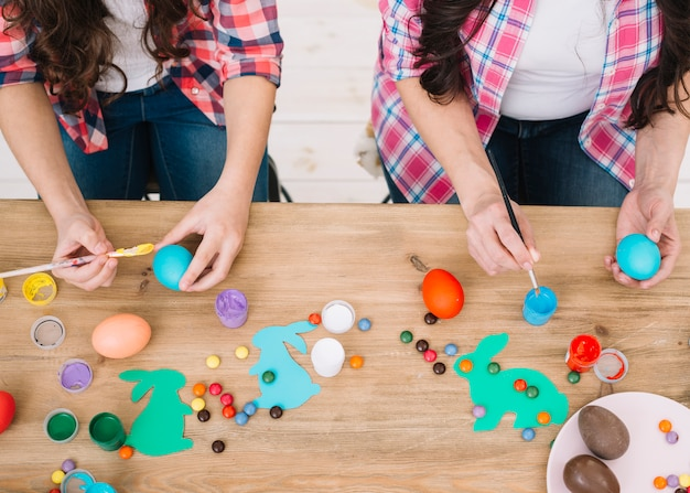An overhead view of mother and daughter painting the easter eggs over the wooden table