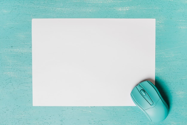 An overhead view of mouse on blank white paper against turquoise background