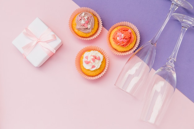 An overhead view of muffins; wrapped presents and transparent champagne on pink and purple backdrop
