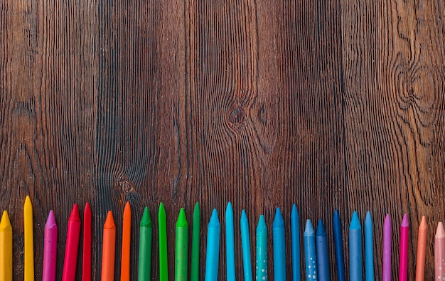 Overhead view of multicolored wax crayons arranged in row at bottom of the background