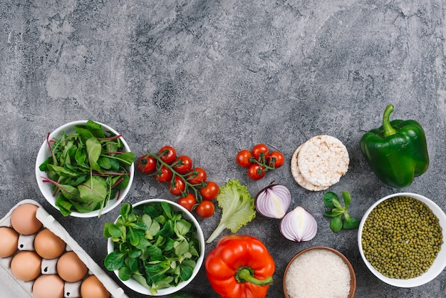 An overhead view of mung bean; eggs; spinach; vegetables; lettuce and puffed rice cake on concrete background