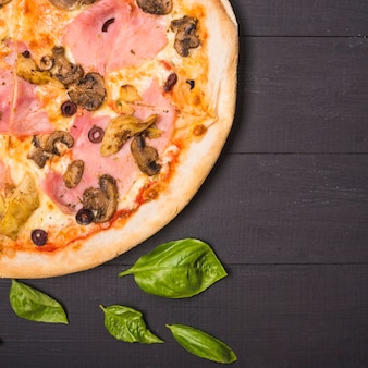 An overhead view of mushroom and meat pizza with basil leaves on wooden plank