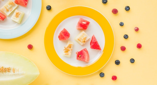 An overhead view of muskmelon and watermelon slices on plate with blueberries and raspberries