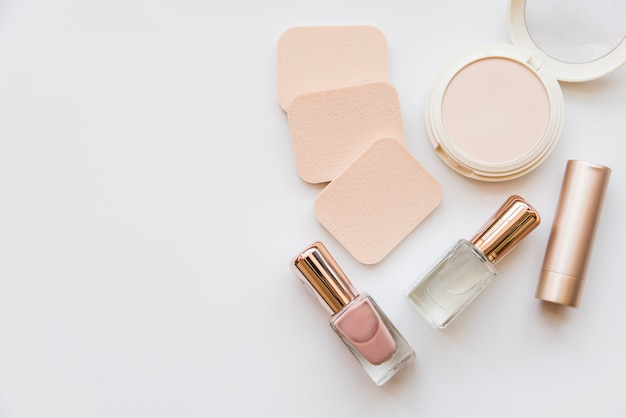 An overhead view of nail polish bottle; lipstick; sponge and compact on white background