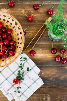 Overhead view of napkin; rosemary and red cherries in wicker bowl