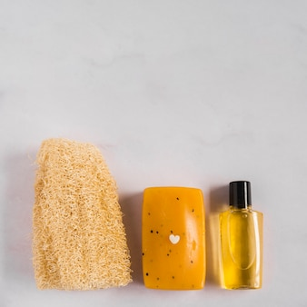 An overhead view of natural loofah; herbal soap and essential oil bottle against white background