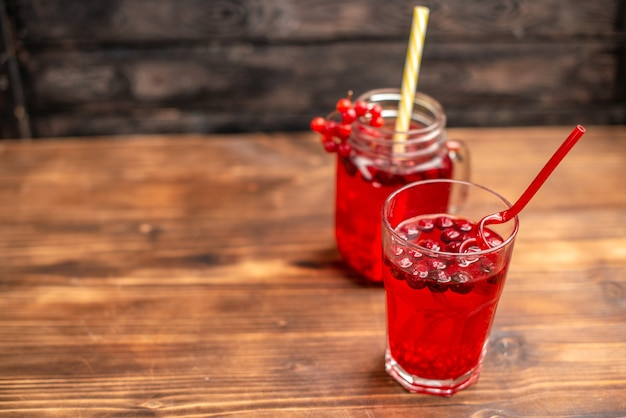 Overhead view of natural organic fresh currant juice in a glass and a bottle served with tubes on th left side on a wooden table