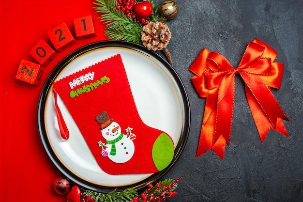 Vista dall'alto del fondo del nuovo anno con il calzino di natale sugli accessori della decorazione del piatto della cena rami di abete e numeri su un tovagliolo rosso e nastro rosso su un tavolo nero