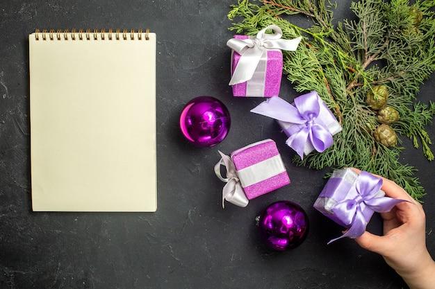 Vista dall'alto dei regali di capodanno per i membri della famiglia e degli accessori decorativi accanto al notebook su sfondo nero