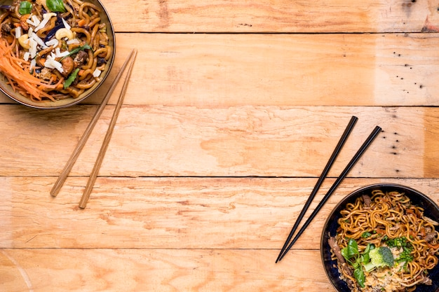 An overhead view of noodles bowls with chopsticks on wooden plank