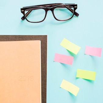 Overhead view of notebook; adhesive notes and spectacles on colored background