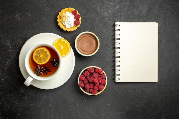 Overhead view of notebook and a cup of black tea with lemon served with chocolate raspberry honey on dark background