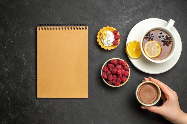 Vista dall'alto del taccuino e una tazza di tè nero al limone servito con miele di lampone al cioccolato su sfondo scuro