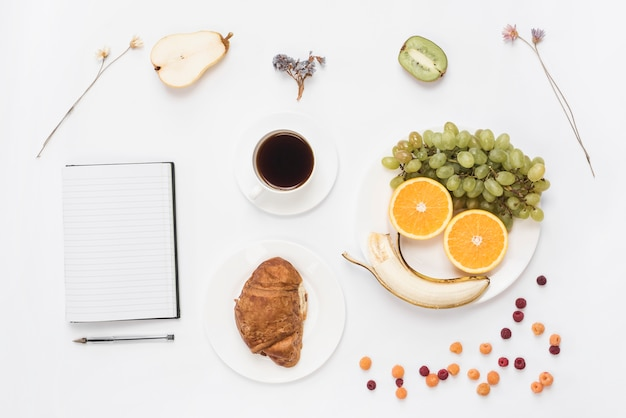 An overhead view of notebook; pen; croissant; fruits; coffee and dried flowers on white backdrop