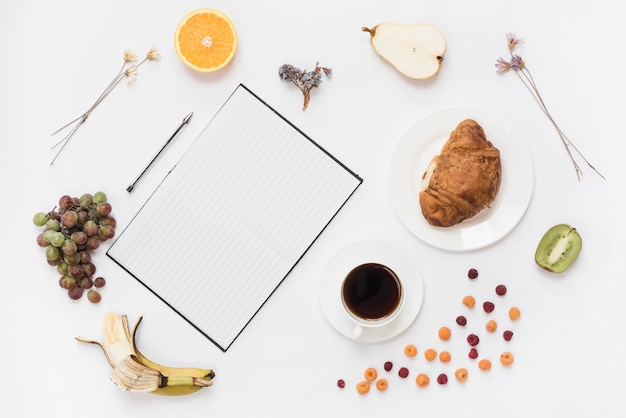 An overhead view of notebook; pen with croissant and healthy fruits isolated on white background