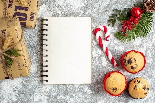 Overhead view of notebook and small cupcakes candy and fir branches decoration accessories and gifts on ice surface