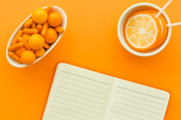 Overhead view of notepad with lollipops and candies on orange backdrop